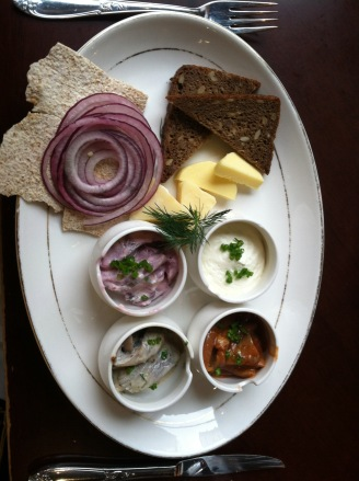 Four types of herring with bread, cheese, and crackers.