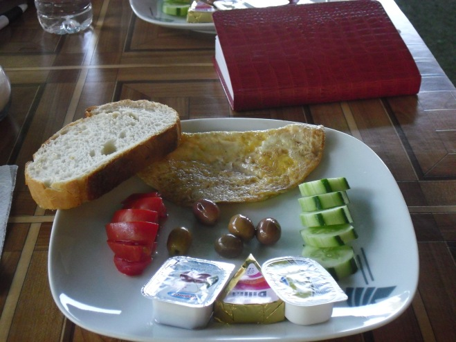 Toast, tomato, olives, cucumber, and cheeses
